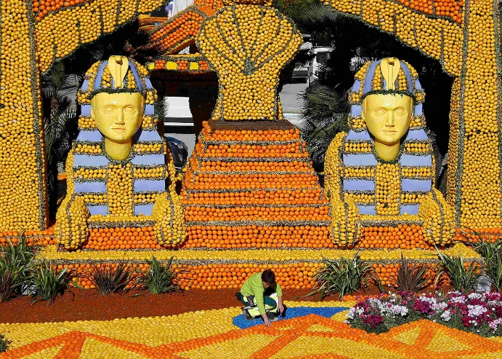 "A worker puts the final touch to a replica of a giant pharaons made with lemons and oranges which shows a scene of the movie ""Cleopatra"" during the Lemon festival in Menton, France, February 10, 2016. Some 140 metric tons of lemons and oranges are used to make displays during the 83rd festival, which is themed ""Cinecitta"", and runs from February 13 through March 2. REUTERS/Eric Gaillard"